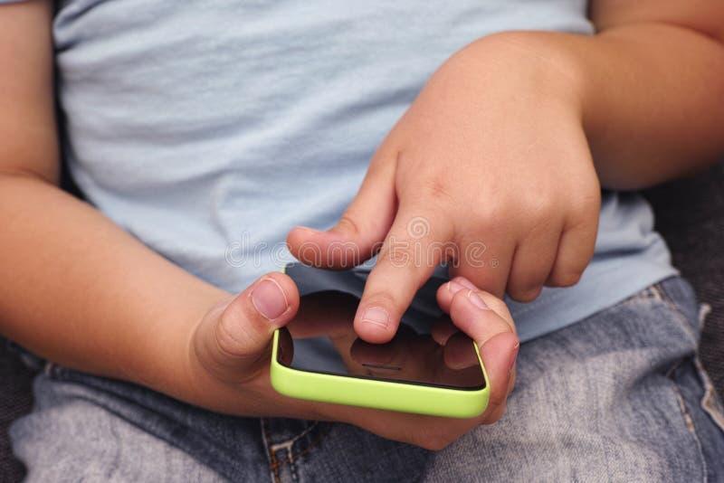 Niño que usa el teléfono elegante móvil fotos de archivo libres de regalías