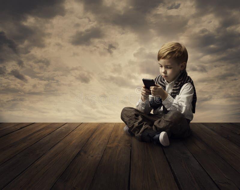Niño que usa el teléfono móvil, muchacho del niño que juega el teléfono fotos de archivo libres de regalías
