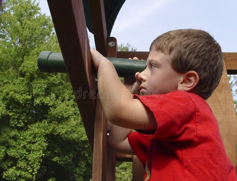Niño que usa el telescopio foto de archivo