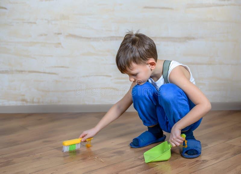 Niño que usa la escoba y el recogedor de polvo del juguete fotografía de archivo