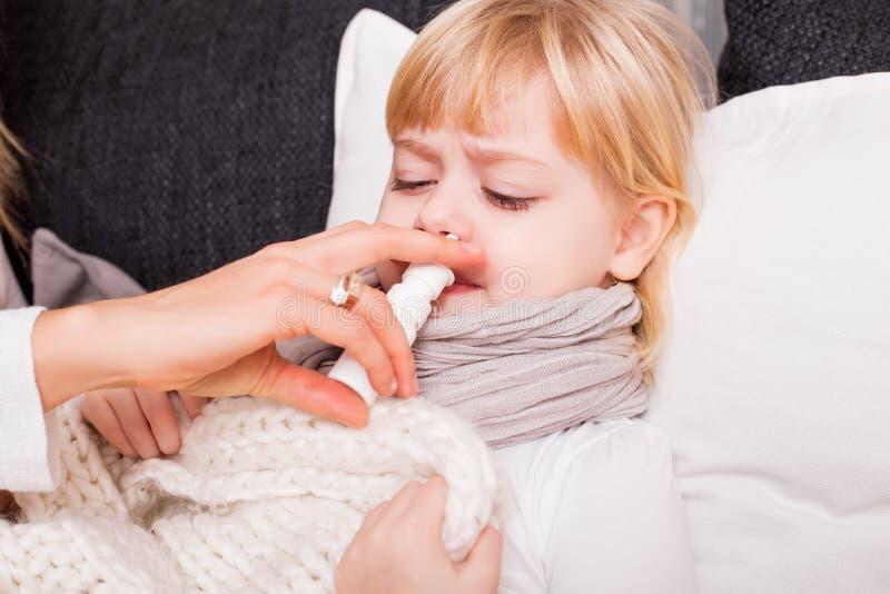 Niño que usa la medicina para tratar frío fotografía de archivo