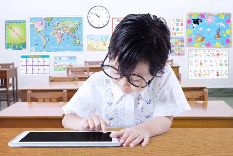 Niño que usa la tableta en el escritorio en clase fotos de archivo libres de regalías