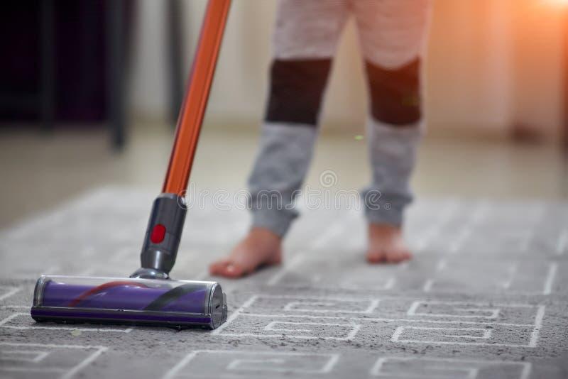 Niño que usa un aspirador mientras que limpia la alfombra en la casa imágenes de archivo libres de regalías