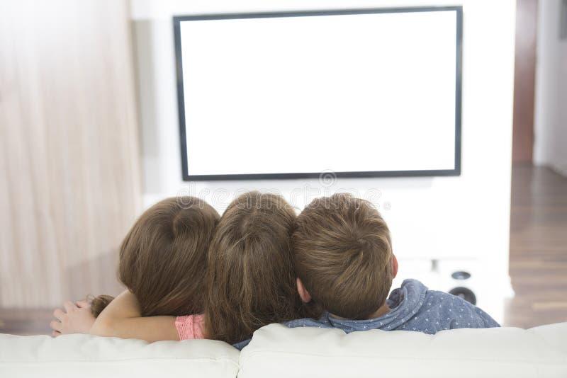 Niño que ve la TV en casa imagen de archivo