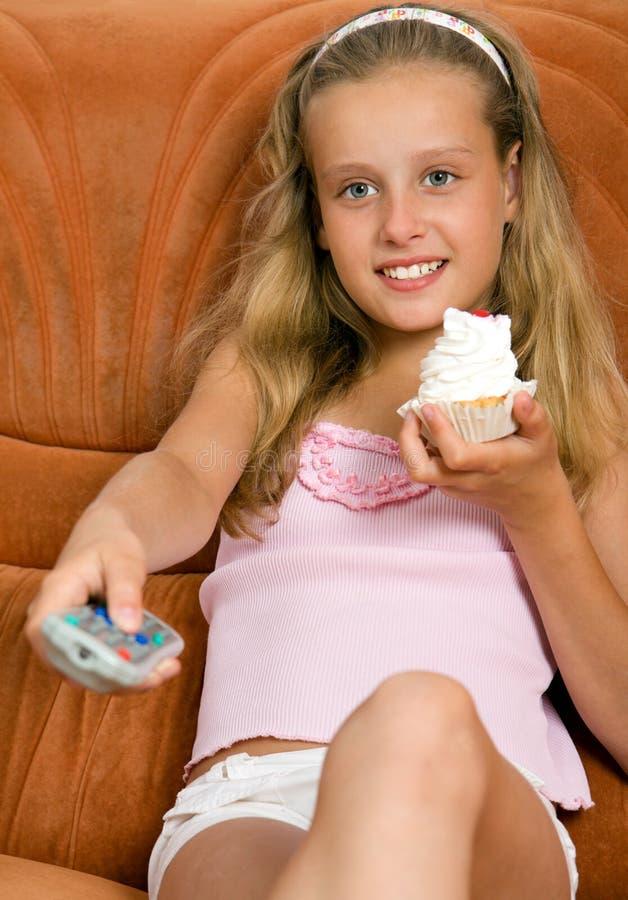 Niño que ve la TV y que come la torta imagenes de archivo
