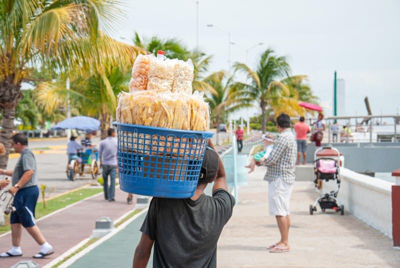 Niño que vende los buñuelos de maíz a lo largo de la 'promenade' marítima de Campeche México imagen de archivo libre de regalías