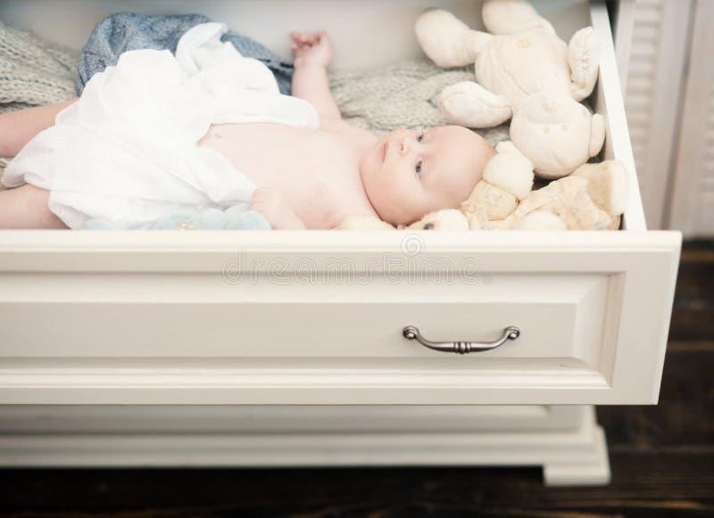 Niño recién nacido con los ojos azules y la cara curiosa Bebé que miente en el cajón de madera blanco del pecho imagen de archivo