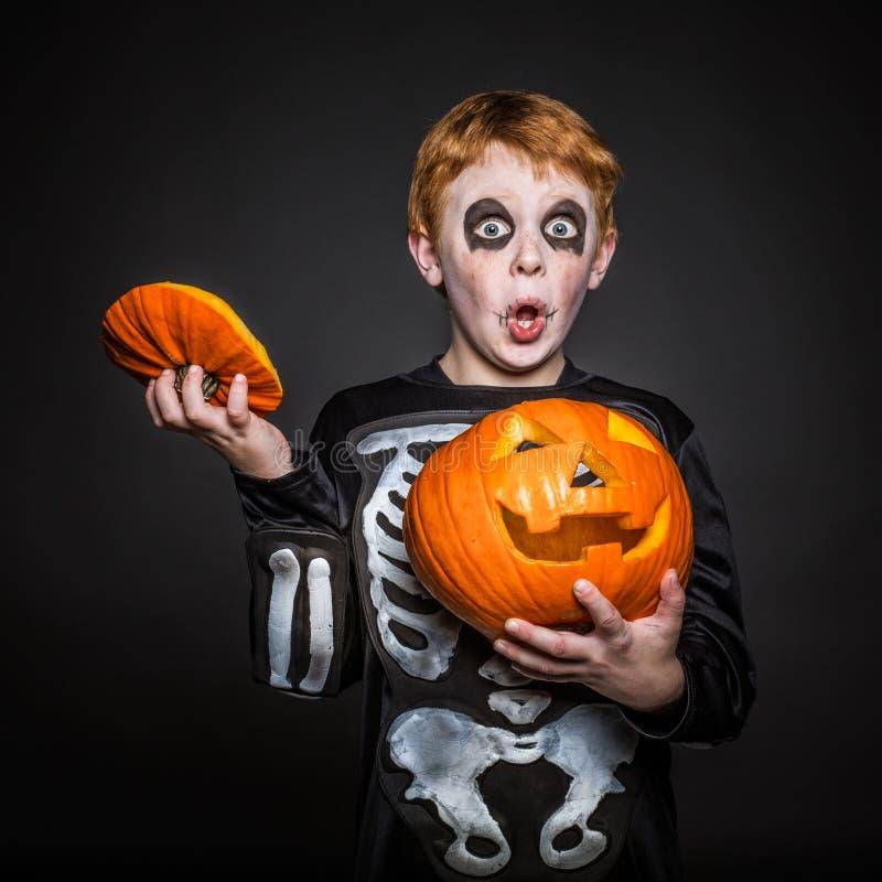 Niño rojo sorprendido del pelo en el traje de Halloween que sostiene una calabaza anaranjada esqueleto foto de archivo