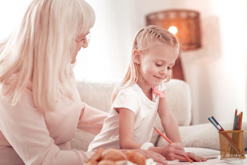 Niño rubio dulce con un lápiz que sonríe feliz imágenes de archivo libres de regalías