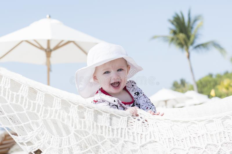 Niño rubio expresivo feliz hermoso de la muchacha con la protección de Sun en una piscina imagenes de archivo