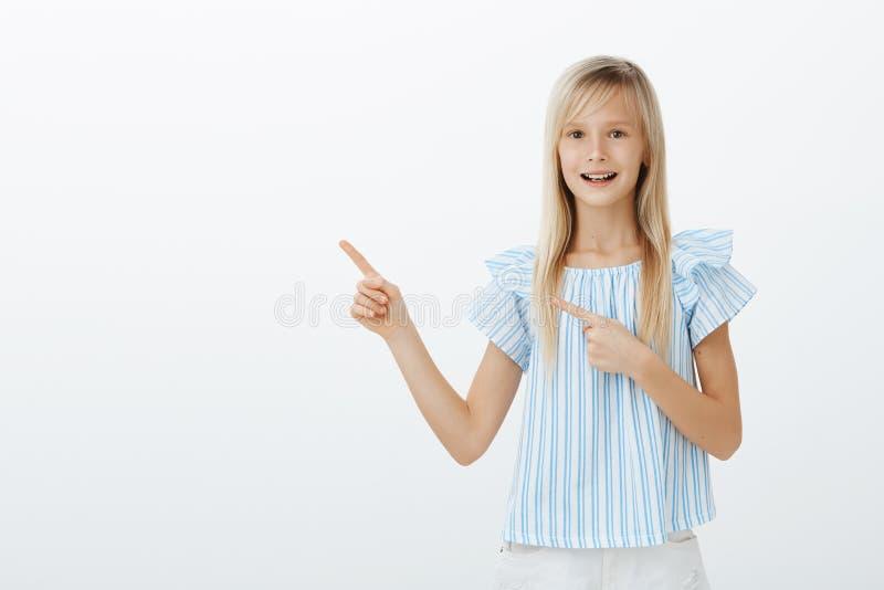 Niño rubio joven contento apuesto en la blusa azul de moda, sintiendo excitada y sorprendida mientras que señala en la parte supe fotografía de archivo
