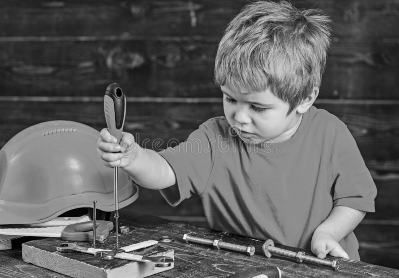 Niño rubio que juega en taller Tornillos obligatorios del muchacho al tablero de madera Niño concentrado que aprende nuevas destr foto de archivo libre de regalías
