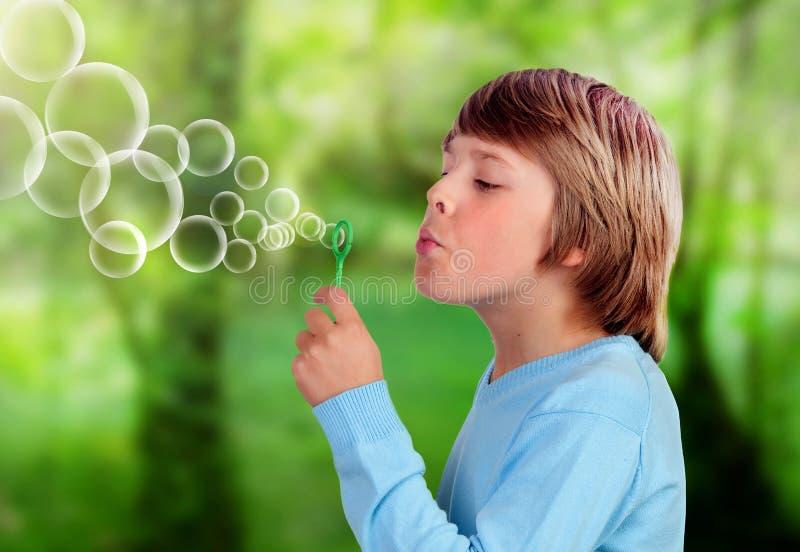Niño rubio que sopla y que hace burbujas imagenes de archivo