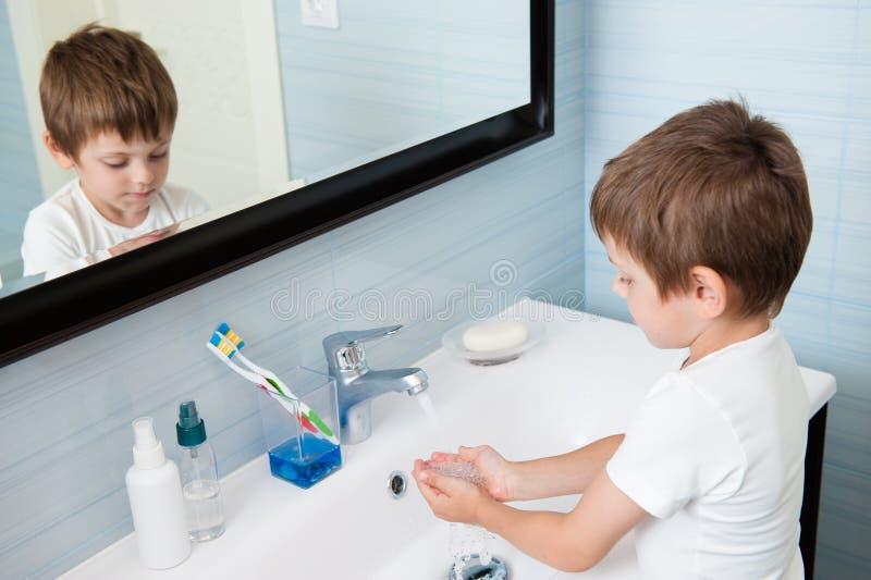 Niño sano lindo que se lava las manos debajo del agua en cuarto de baño por mañana fotos de archivo