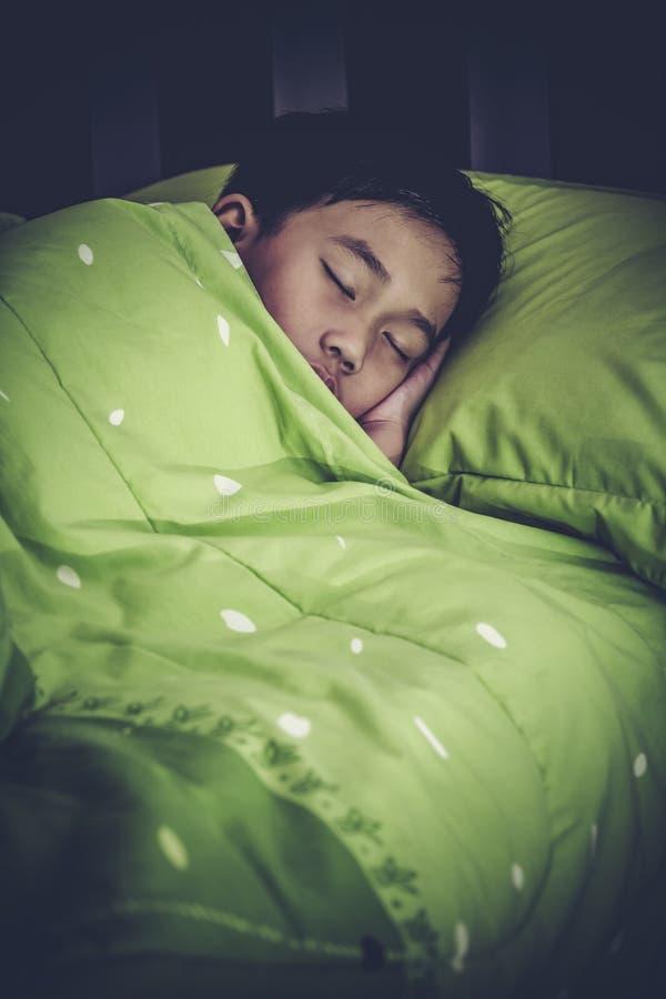 Niño sano Pequeño muchacho asiático que duerme pacífico en cama alto imagen de archivo
