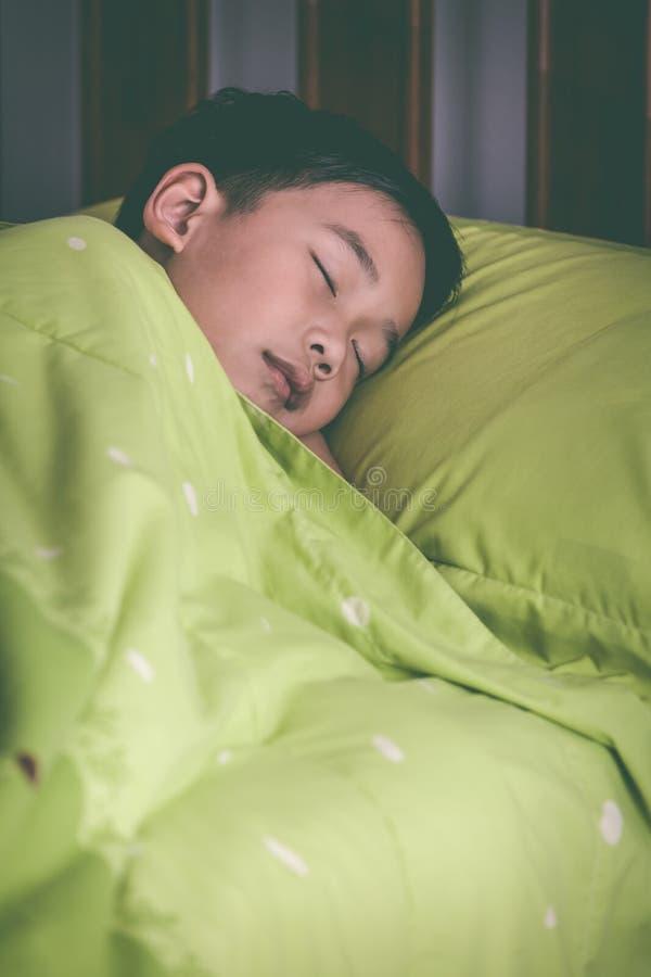 Niño sano Pequeño muchacho asiático que duerme pacífico en cama Vint imagen de archivo