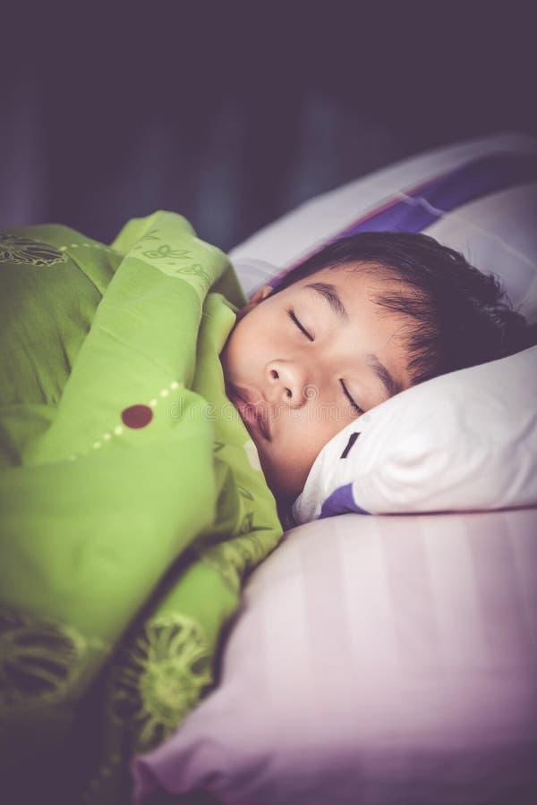 Niño sano Pequeño muchacho asiático que duerme pacífico en cama Vint imágenes de archivo libres de regalías
