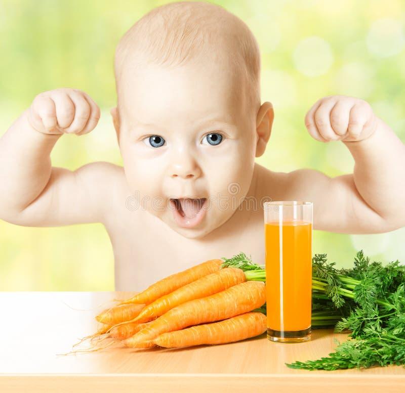 Niño sano y fuerte con el vidrio fresco del jugo de zanahoria fotos de archivo