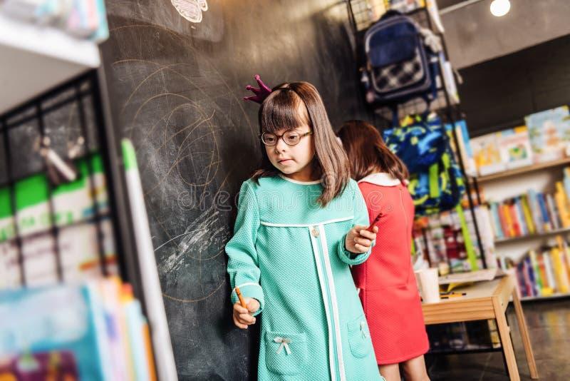niño soleado preescolar Oscuro-cabelludo que lleva el vestido y la corona azules fotografía de archivo libre de regalías