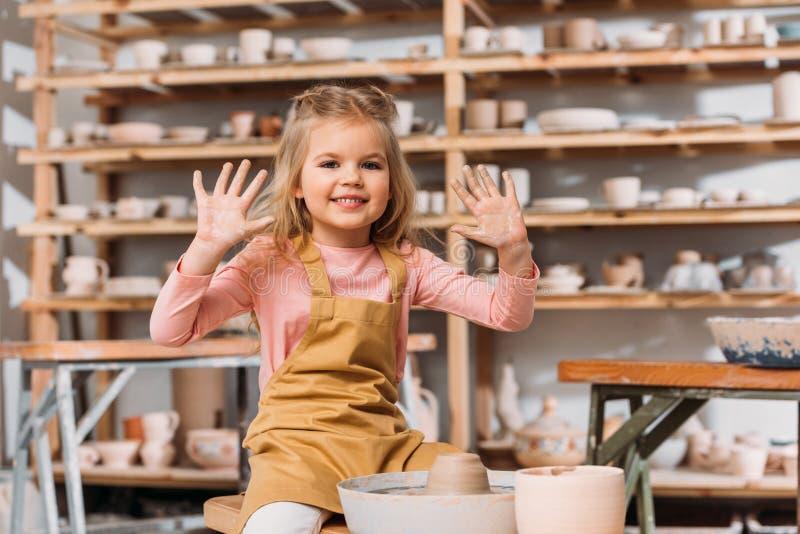 niño sonriente adorable con la arcilla de la rueda de la cerámica que muestra las manos imágenes de archivo libres de regalías