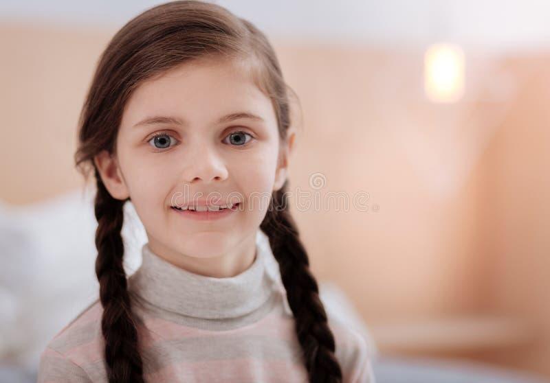 Niño sonriente agradable con los ojos grises grandes imagen de archivo