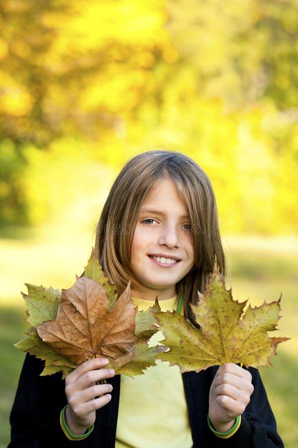 niño sonriente con las hojas de otoño imagenes de archivo