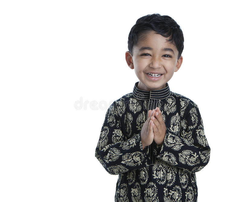 Niño sonriente con las manos plegables foto de archivo