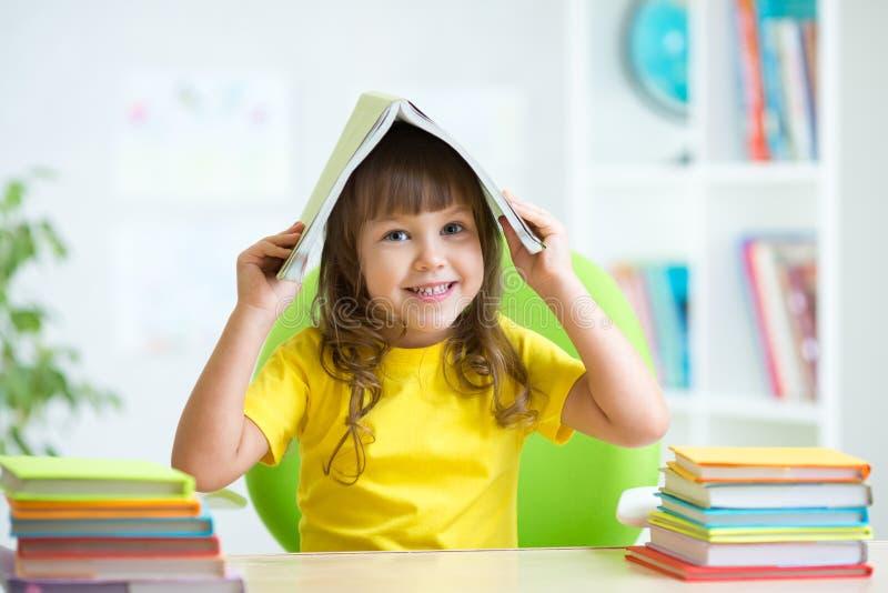 Niño sonriente con un libro sobre su cabeza fotografía de archivo