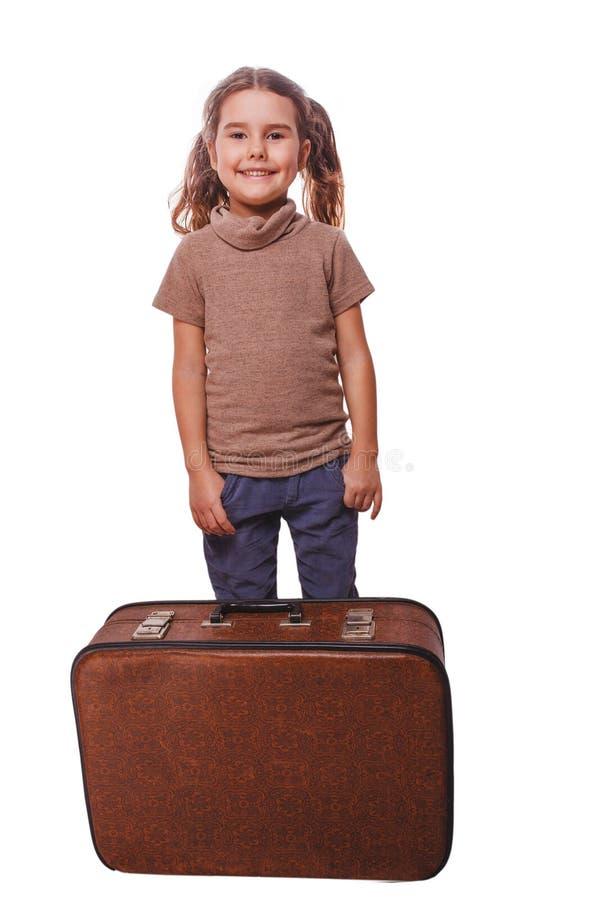 Niño sonriente de la muchacha morena que se coloca al lado de la maleta para el viaje fotografía de archivo