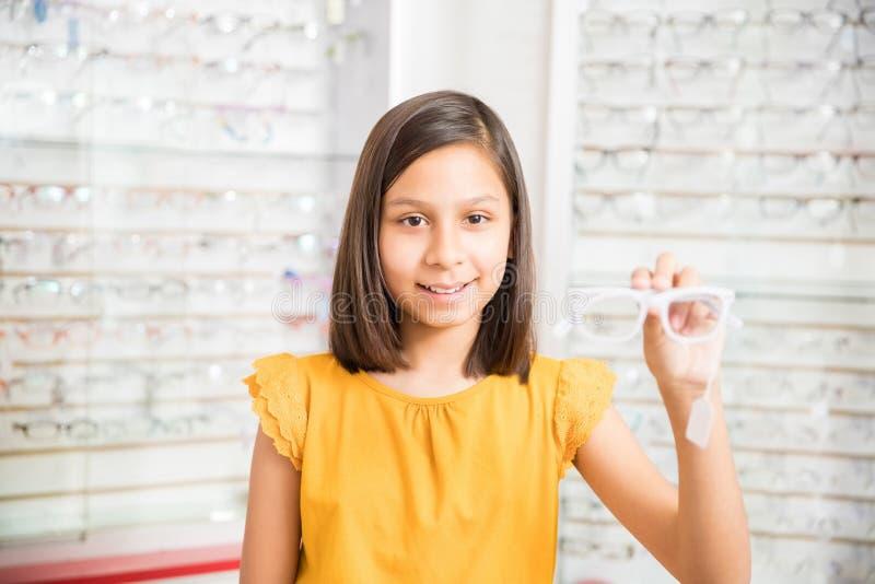 Niño sonriente de la muchacha que decide comprar nuevos vidrios que eligen marcos imágenes de archivo libres de regalías
