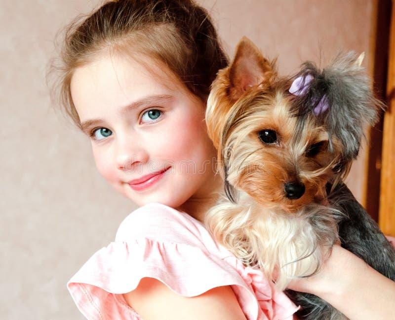 Niño sonriente de la niña que se sostiene y que juega con el terrier de Yorkshire del perrito fotografía de archivo libre de regalías