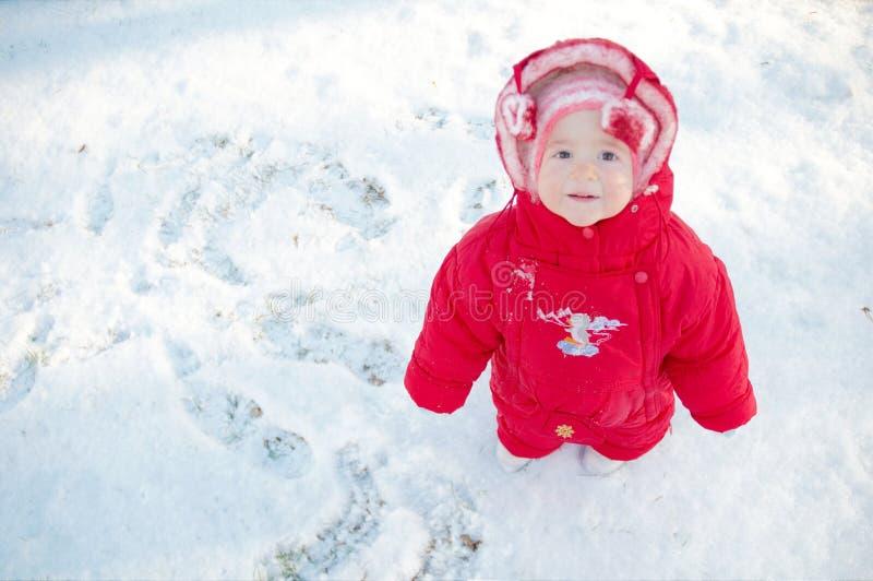 Niño sonriente en una calle nevosa fotografía de archivo