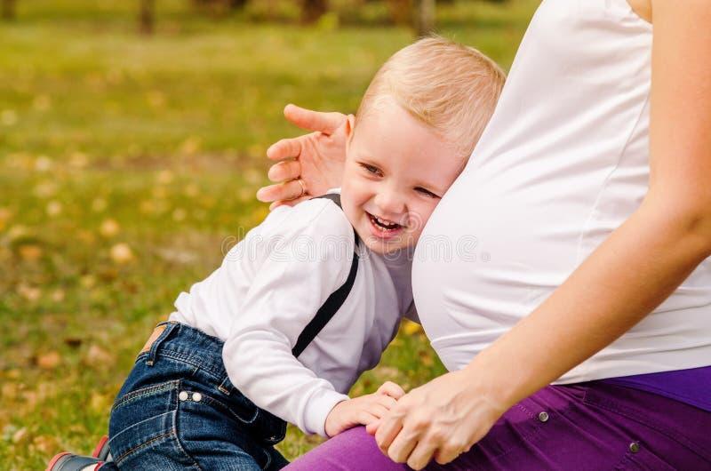 Niño sonriente feliz cerca de la panza embarazada de la mamá imágenes de archivo libres de regalías