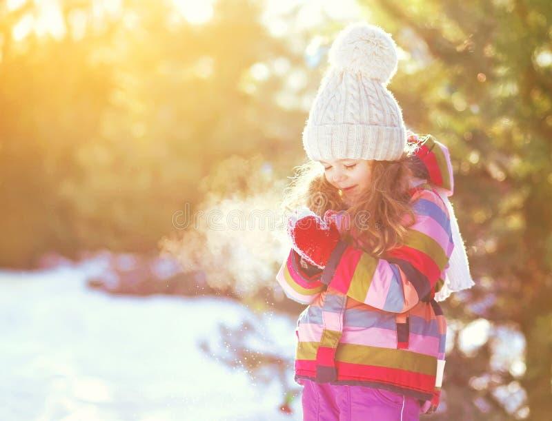 Niño sonriente feliz de la niña del invierno sobre nevoso soleado fotos de archivo