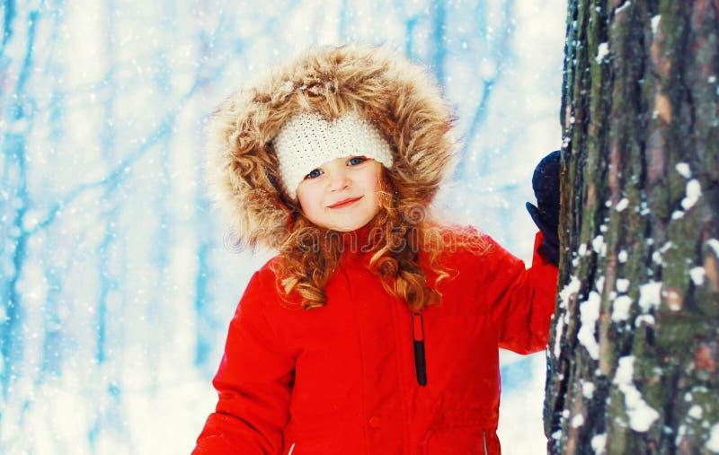 Niño sonriente feliz de la niña del retrato del invierno cerca del árbol sobre nevoso fotografía de archivo libre de regalías