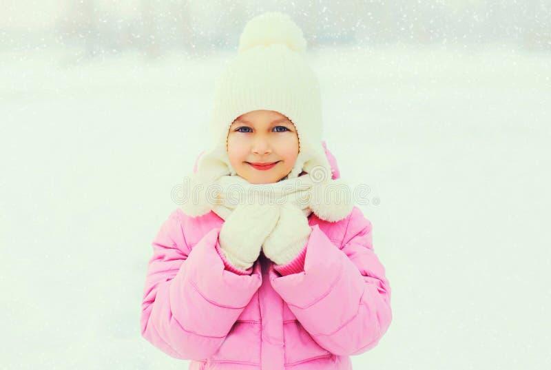 Niño sonriente feliz de la niña del retrato del invierno sobre los copos de nieve imagenes de archivo