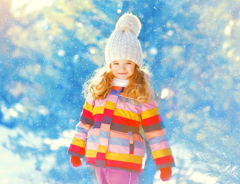 Niño sonriente feliz de la niña del retrato del invierno sobre nevoso foto de archivo