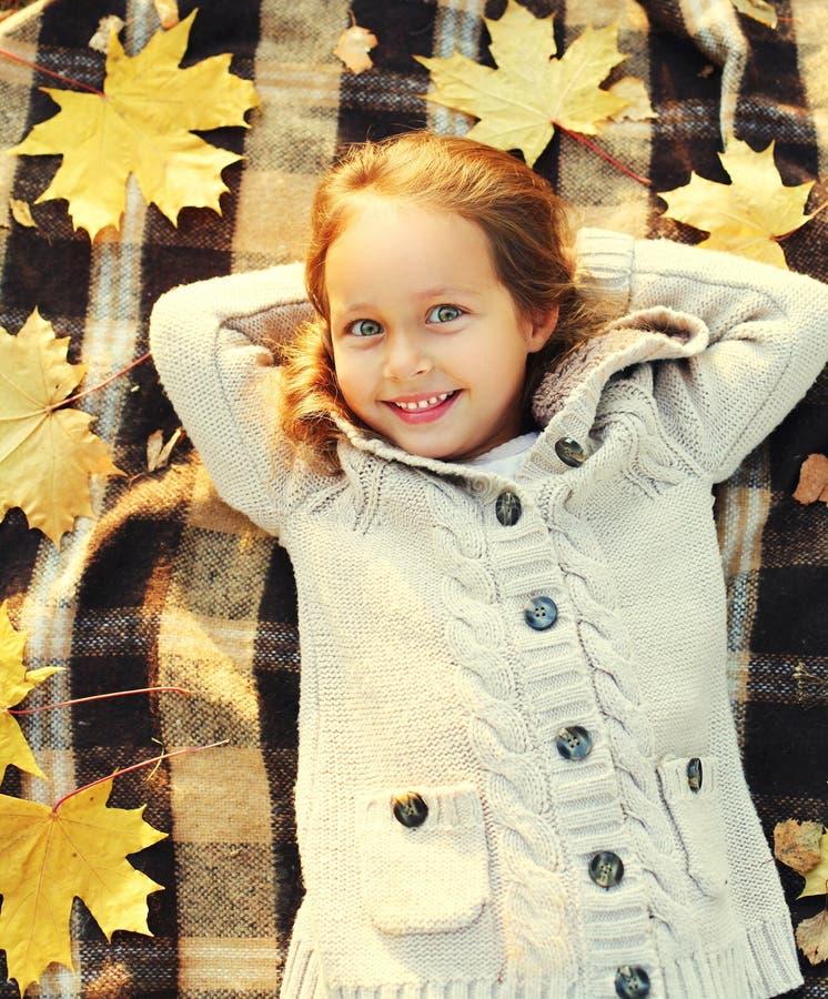 Niño sonriente feliz de la niña del retrato que miente divirtiéndose con las hojas de arce amarillas en top soleado del día del o fotografía de archivo