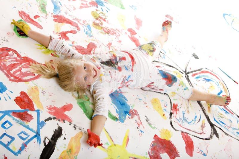 Niño sonriente feliz por completo con el color (pintura) foto de archivo