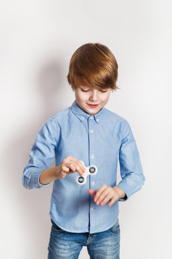 Niño sonriente feliz que juega con el hilandero blanco foto de archivo