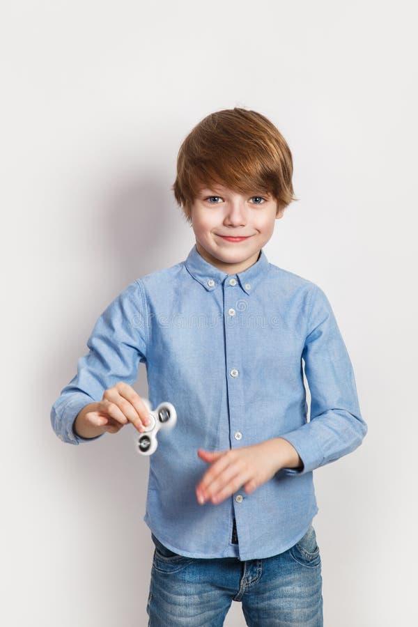 Niño sonriente feliz que juega con el hilandero blanco imagenes de archivo