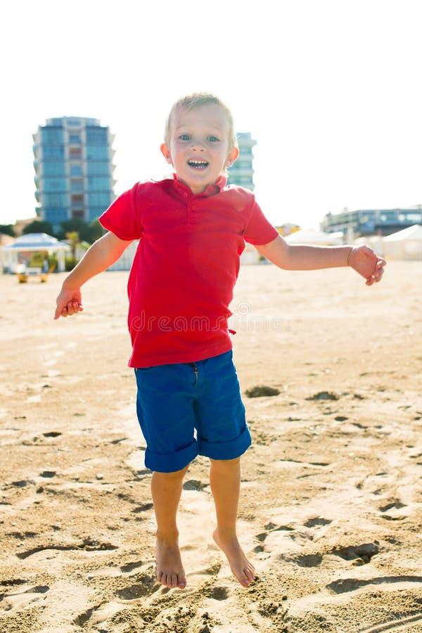 Niño sonriente hermoso feliz que salta en la playa de la arena, mirando la cámara foto de archivo libre de regalías