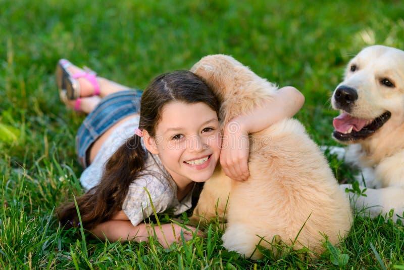 Niño sonriente que abraza un perrito imagen de archivo libre de regalías