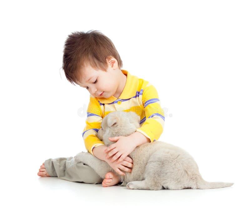 Niño sonriente que abraza un perrito fotografía de archivo libre de regalías