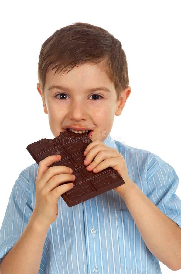 Niño sonriente que come el chocolate imágenes de archivo libres de regalías