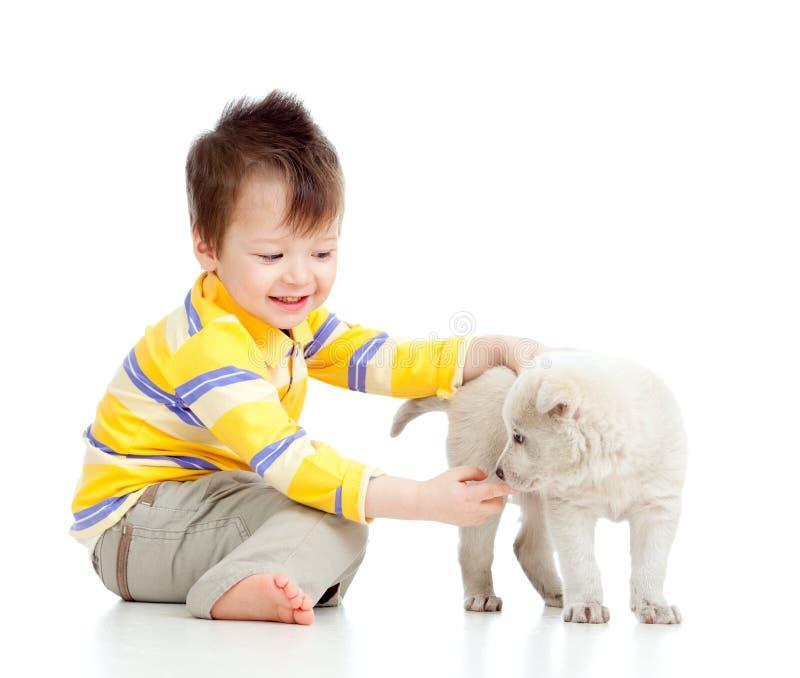 Niño sonriente que juega con un perrito fotografía de archivo
