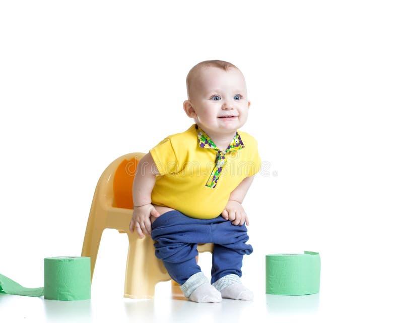 Niño sonriente que se sienta en el pote de cámara con el retrete foto de archivo libre de regalías