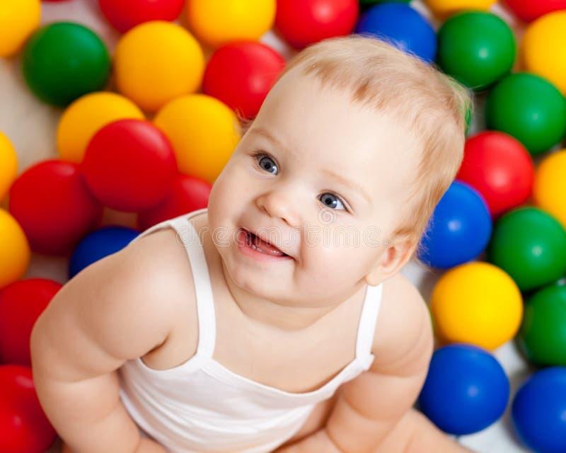 Niño sonriente que se sienta entre bolas coloridas fotografía de archivo