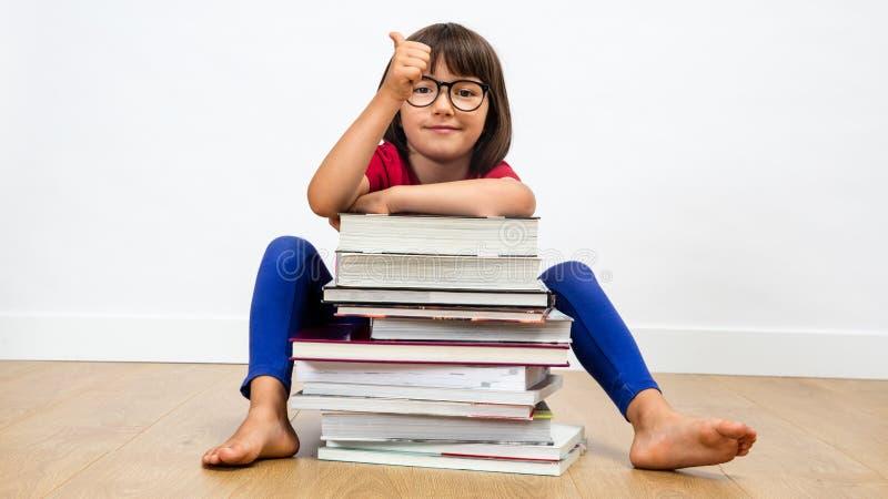 Niño sonriente que sienta detrás de muchos libros con los pulgares para arriba imagen de archivo