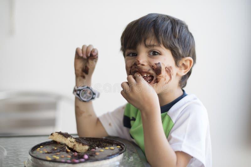 Niño sucio que come la empanada del chocolate foto de archivo
